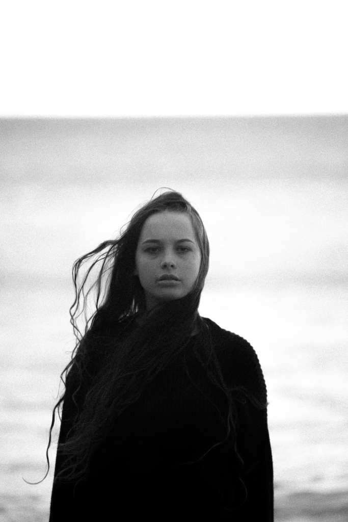a woman stands on a beach with her hair blowing around her