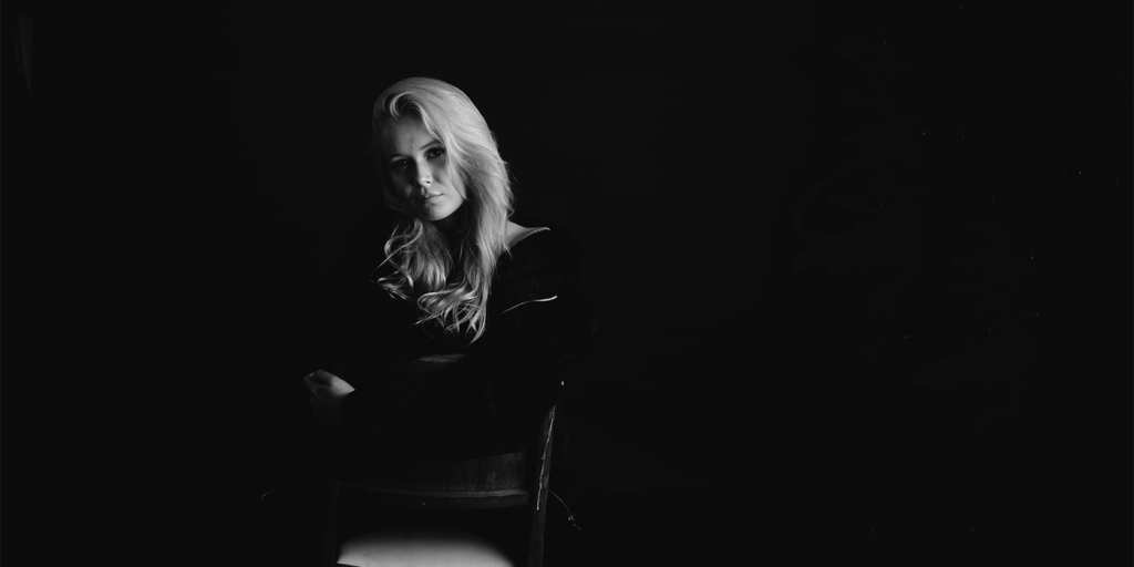A black and white portrait of a woman with blonde hair as she sits in a dark space