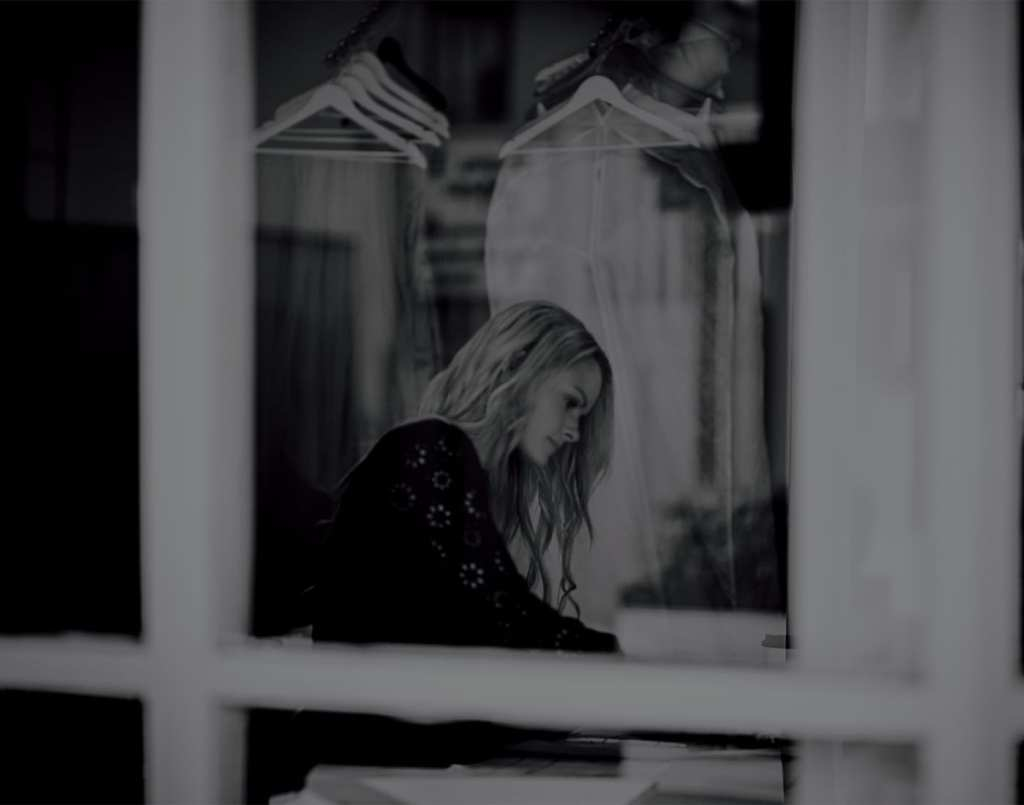 A black and white photo of a woman seen through a window as she sits at a table in a bridal shop