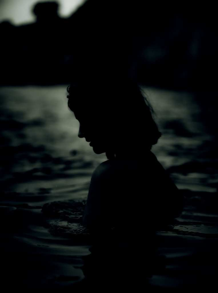 a silhouette of a woman in water