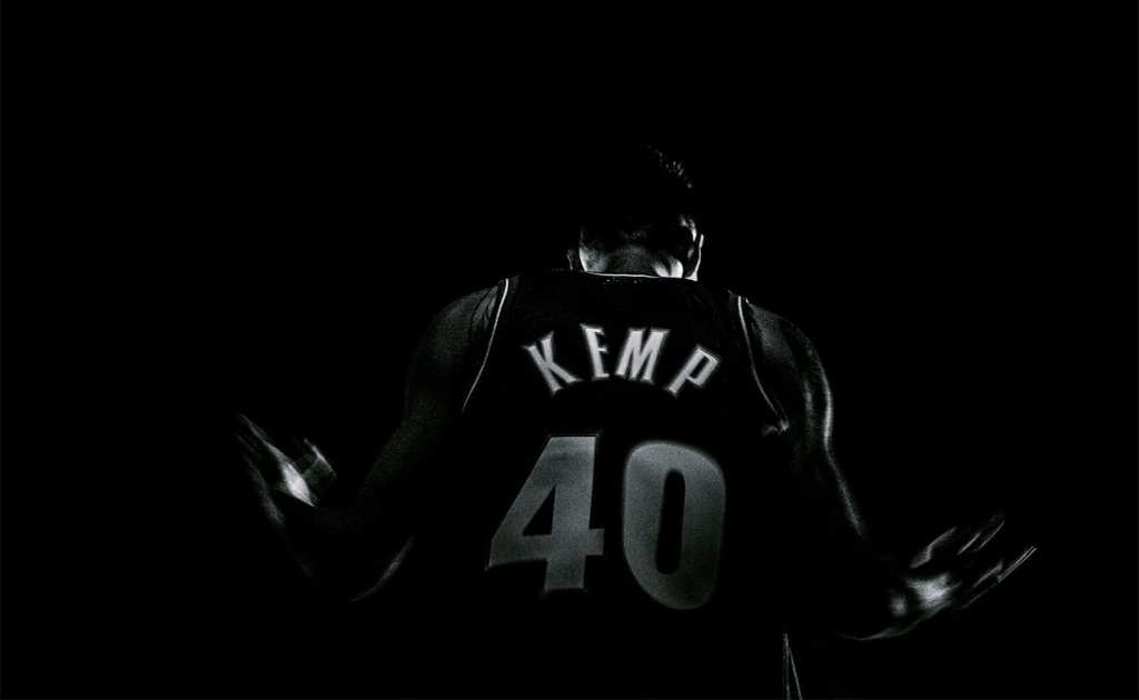 a black and white picture of the back of a man wearing a basketball top