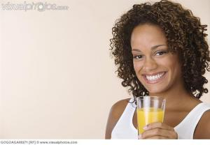 African woman holding glass of juice