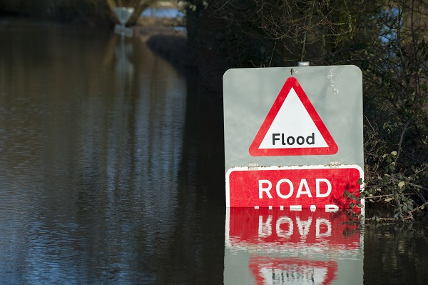 road sign warning for flooding virtually submerged by water