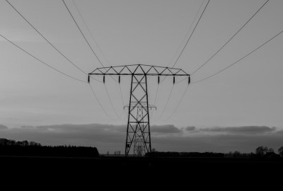 greyscale image of electricity pylon in a field