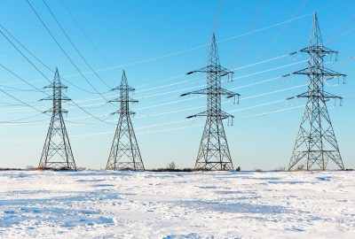 four electricity pylons in snowy field with sunny blue sky