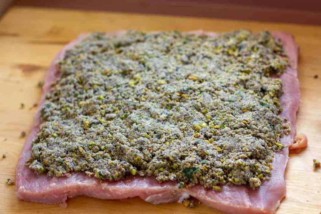 Evenly spread the filling on the flattened pork loin.