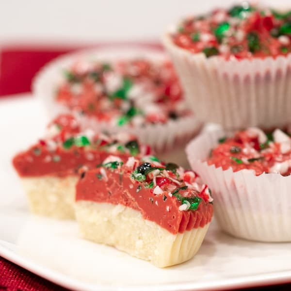 A sweet mini candy cup made with melted white chocolate, crumbled shortbread, crushed candy canes and red candy melts. The perfect sweet treat for Christmas holidays.