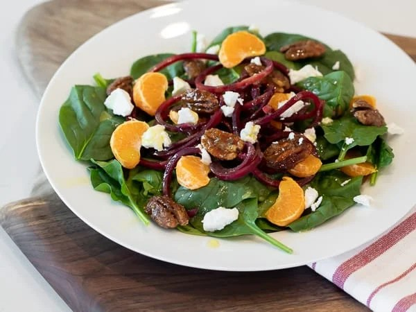 Fresh and healthy salad recipe made with baby spinach, spiralled beets, mandarin oranges, candied pecans and crumbled goat cheese with a honey dijon vinaigrette.