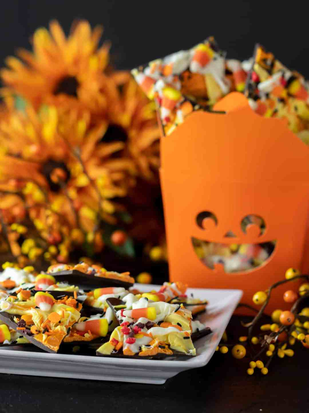 Plate of candy bark and a jack o lantern gift box filled with chocolate bark