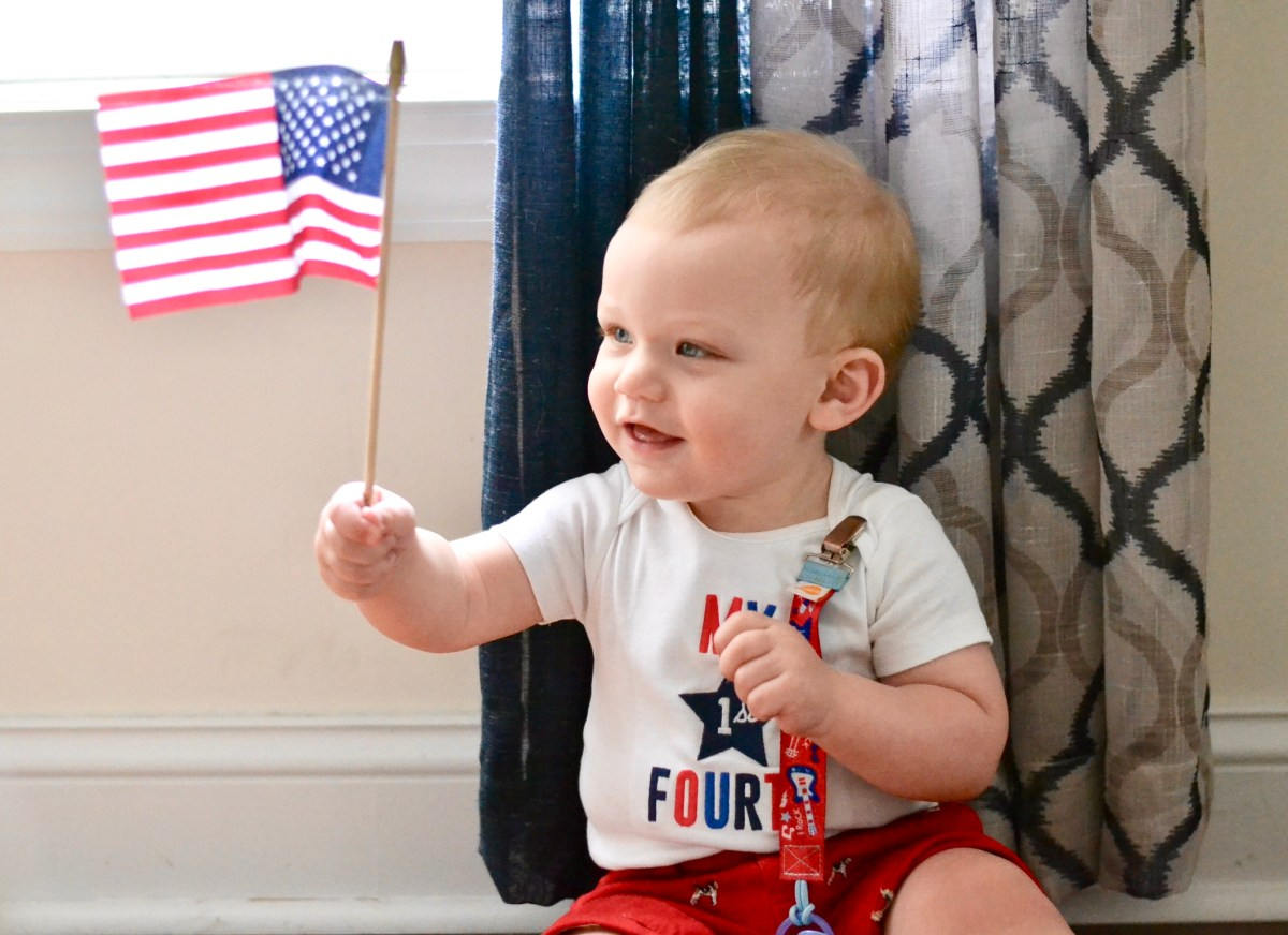"baby holding an American flag in a ""My 1st 4th of July"" onesie"