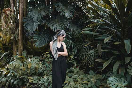 stylish woman standing in tropical garden