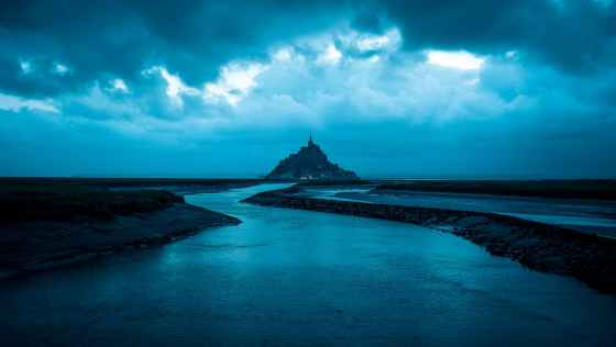 [blue sea under blue sky. a castle sits atop an island in the distance.]