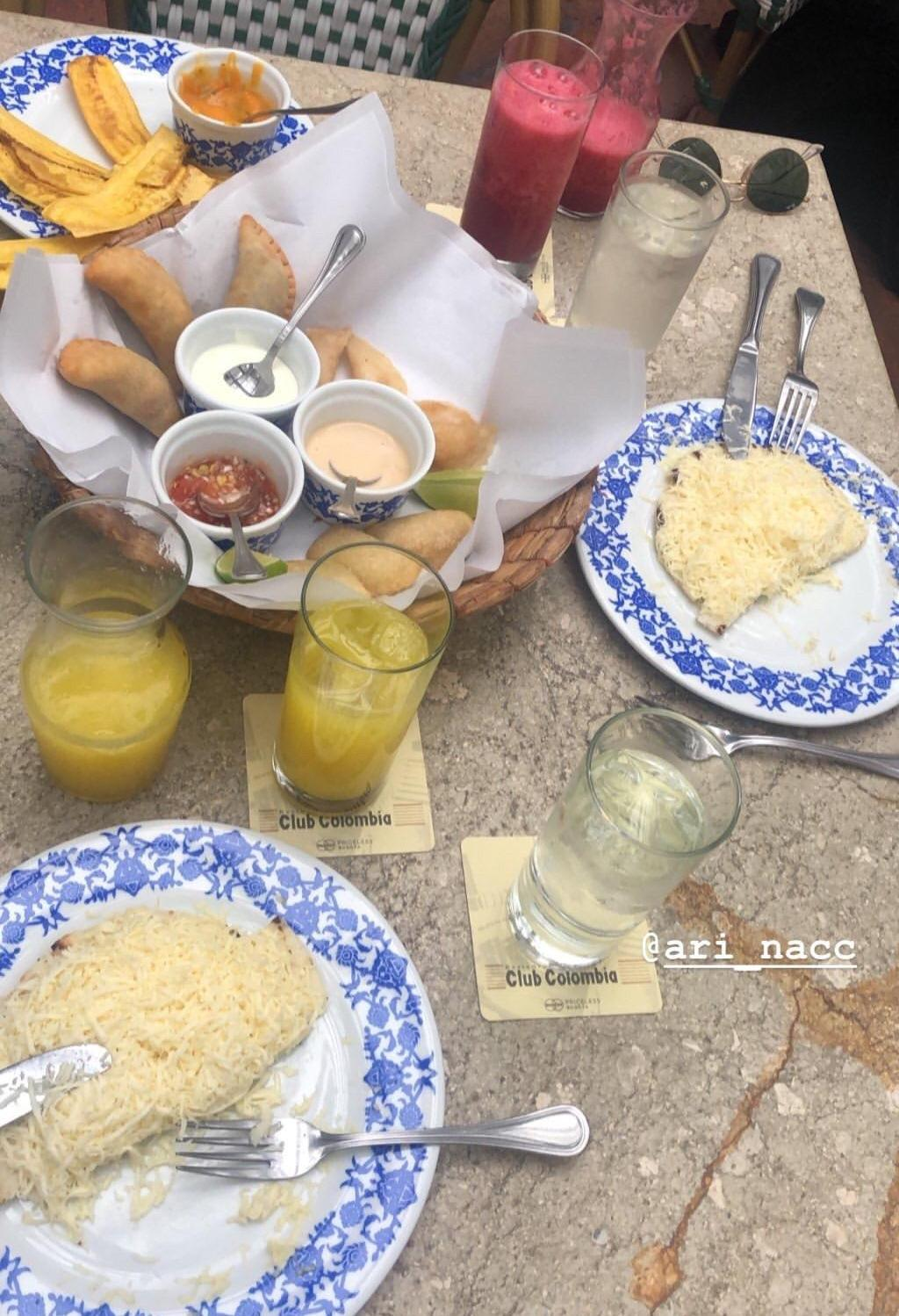 Breakfast table set up with cheese and arepas, empanadas and juices.