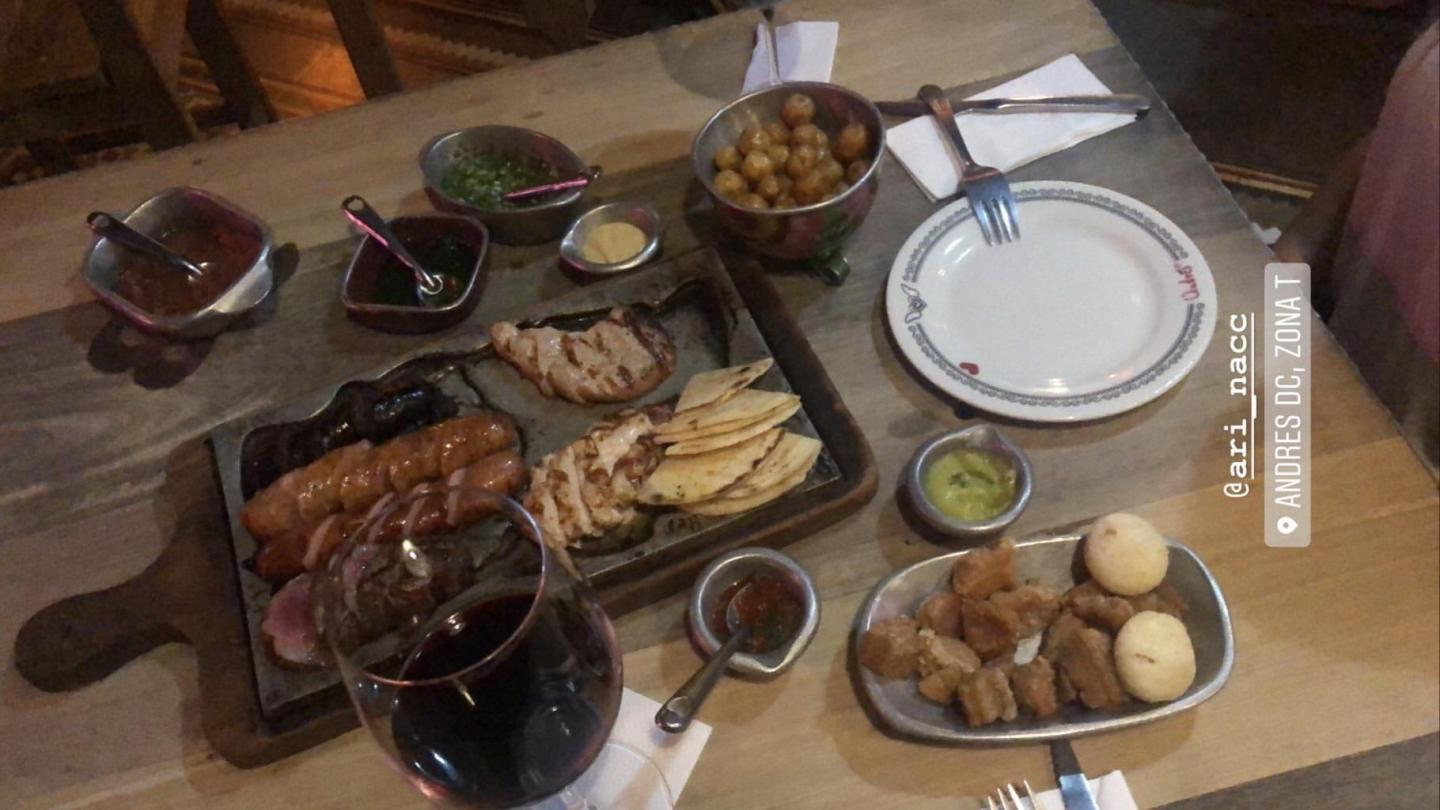 Table with meats, sausages, olives and wine glasses.