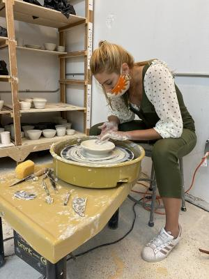Blonde woman molding a pottery plate on a wheel as a hobby.