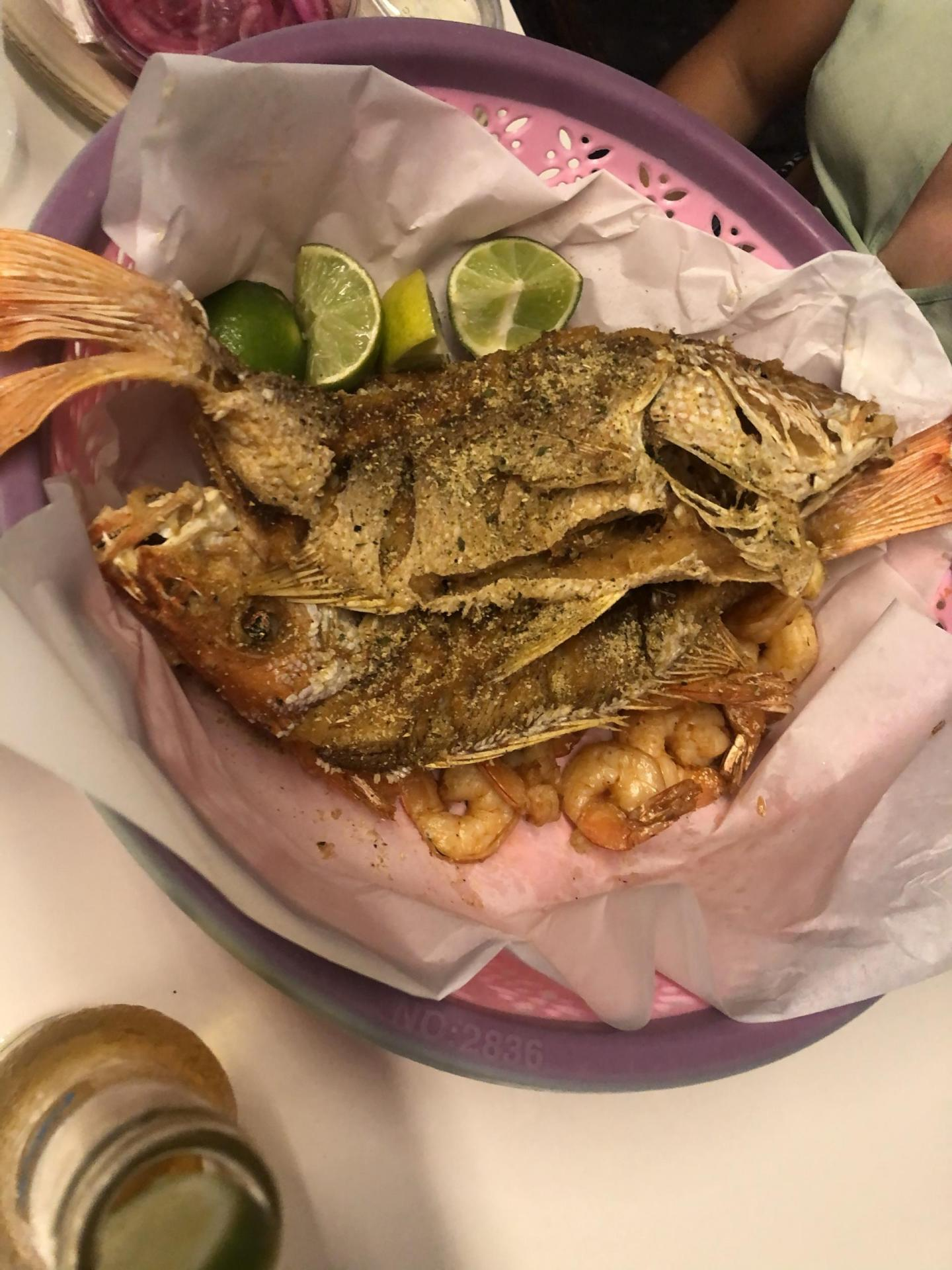 Picture of two fried fish with lime and shrimps.
