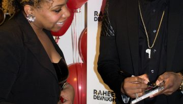 Raheem DeVaughn signs CD cover.