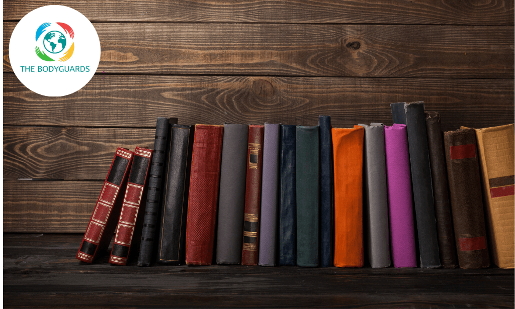 Multi coloured books on a dark wooden background illustrating the Statutes of The Bodyguards