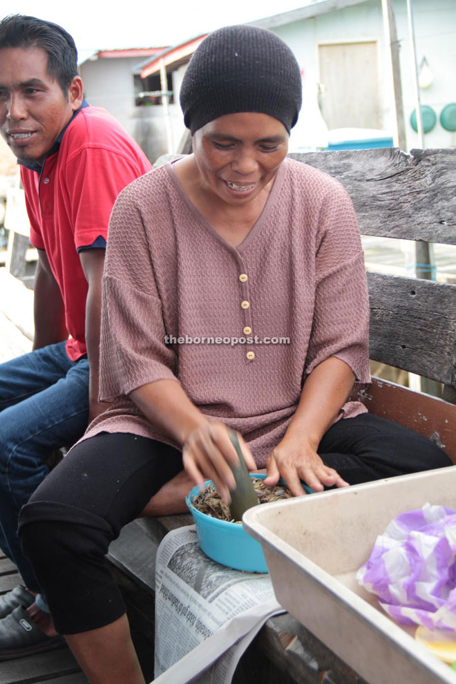 A villager pounds the smoked fish to be made into Sambal Ikan Tahai.