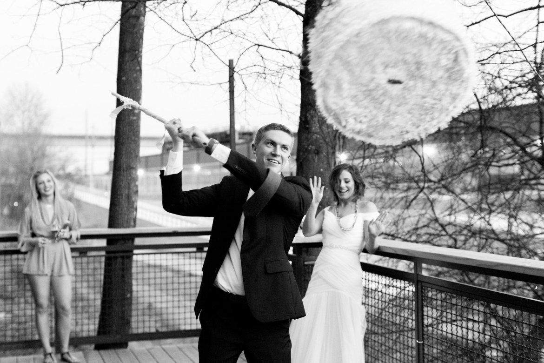 groom smashing DIY wedding cake pinata
