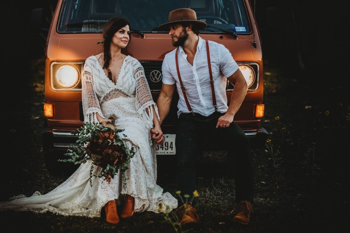 Bride and groom posing next to a combi van