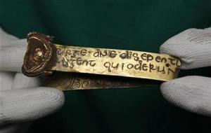 A strip of gold bearing a Biblical inscription is held by a member of museum staff in Birmingham, central England
