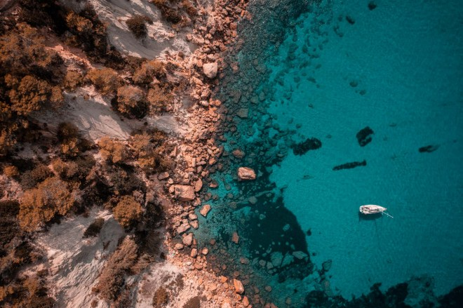 Drone shot of a yacht anchoered in Ibiza, near the shoreline.