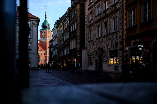 Wonderful Warsaw. The Royal Castle in Warsaw, illuminated with the evening sun beyond a dark street.