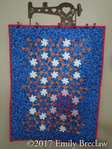 mini-Starburst quilt, featuring blue, orange, white and pink colors, from the book Adventures in Hexagons