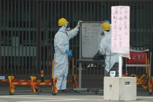 Guards at whiteboard at Fukushima-1 main gate