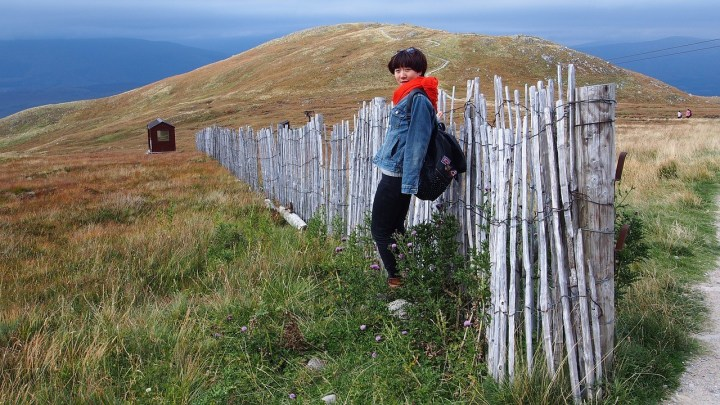 Tourist standing by a length of fence which stretches from nowhere to nowhere across a Scottish moor