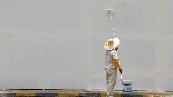 A person finishing painting a large wall white
