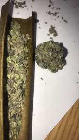 A blunt wrap filled with purple weed on a wooden table.
