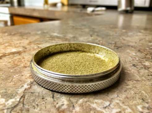 the bottom piece of a grinder filled with a green powder called kief. the grinder sits on a granite countertop.
