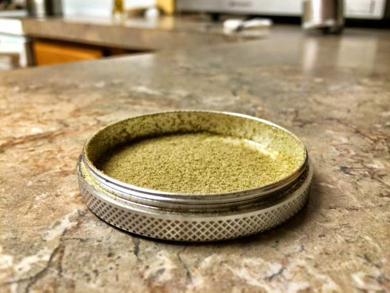 a silver grinder is filled with green shards of kief.