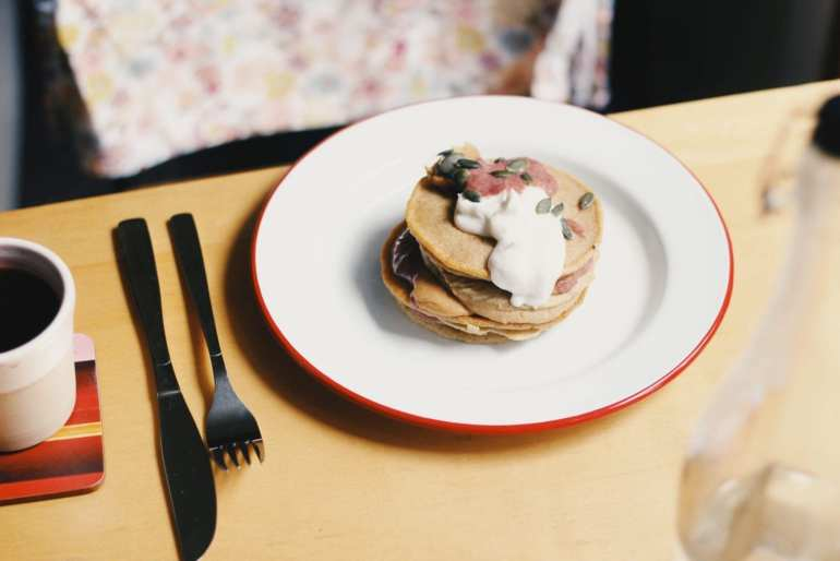 Pancakes on a white plate with a knife and fork beside them on a wooden table
