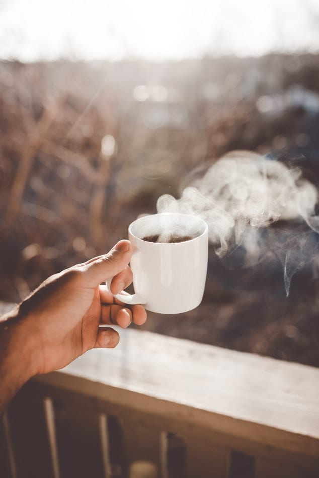 Hand holding a white mug with brown hot coffee which has kief infused into it.