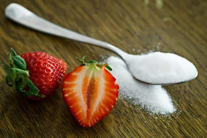 Cannabis infused sugar in a spoon on a table with a strawberry beside it.