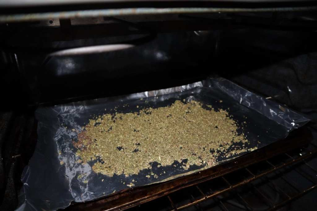 Decarboxylated cannabis on a baking sheet in an oven.