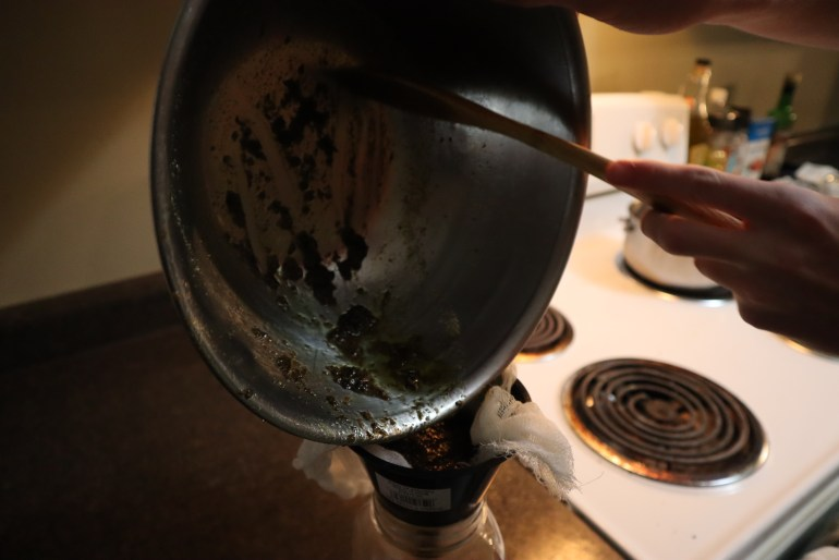 cannabutter being removed from double boiler.