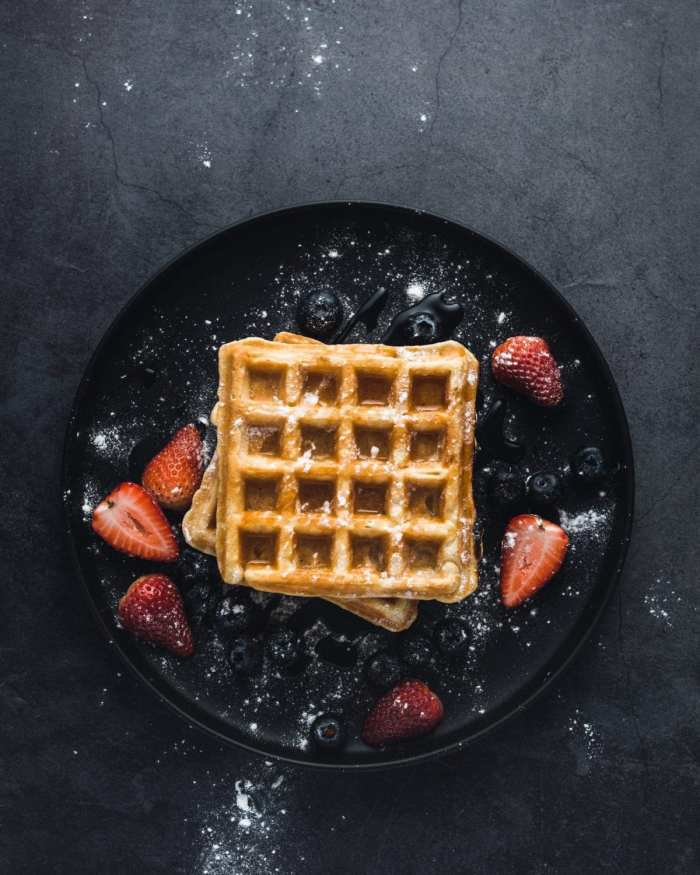 cannabis infused waffle on a black plate with maple syrup poured overtop of them. Strawberries and icing sugar spread around on the black plate.