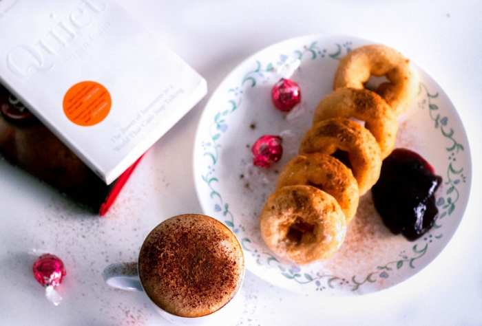 cannabis infused donuts on a white plate with jam and chocolates beside them. Kief coffee with brown sugar beside the plate on a table with 2 books along side