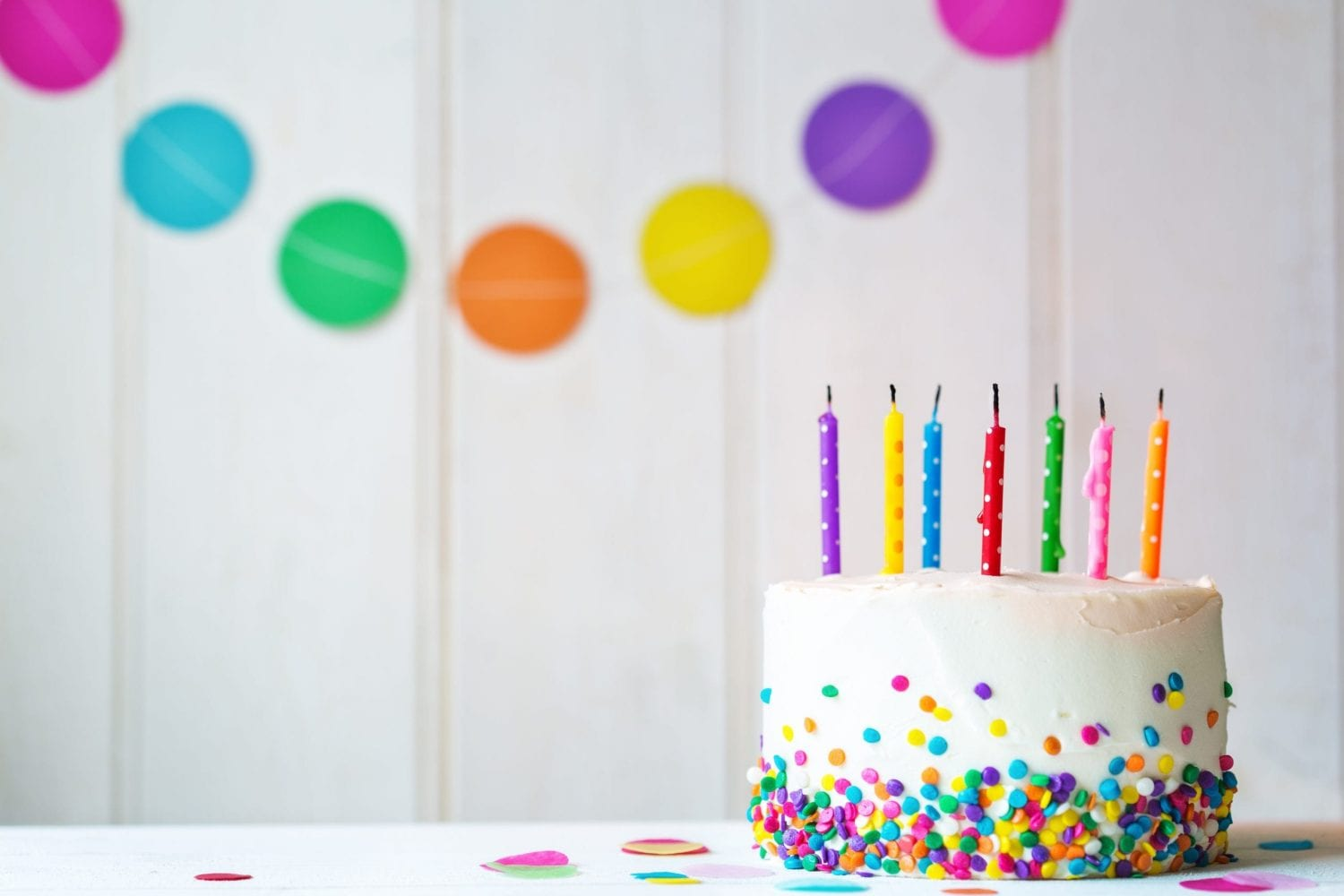 Cannabis birthday cake with sprinkles on the side of it with blown out candles in front of a wall with birthday decorations on it.