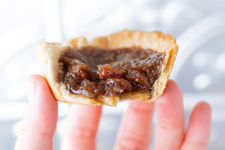 Persons hand holding up a cannabis butter tart in their finger tips.
