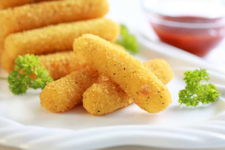 Macro shot of weed mozzarella sticks with sauce and more mozzarella sticks in the background