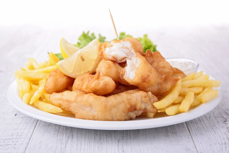 weed fish and chips on a white plate with lemon and salad in the background. A weed edible dinner recipe.