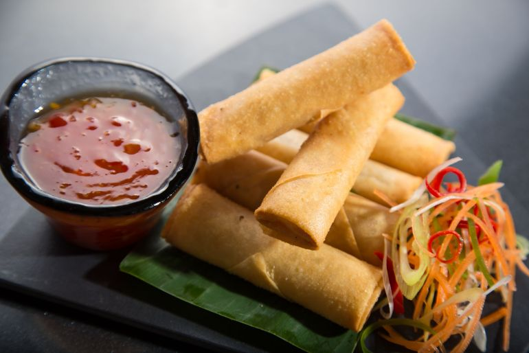 For cannabis infused spring rolls on a black plate with two Kabah spring rolls make it a TP on top of them. Sweet-and-sour sauce and veggies beside the spring rolls on the plate. A weed appetizer recipe.