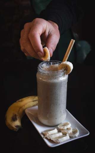 Cannabis banana milkshake on a plate with a persons hand dropping a banana into the milkshake
