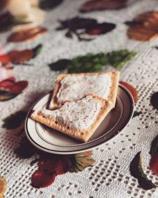 Two cannabis infused pop tarts on a plate which is on a tablecloth with berries
