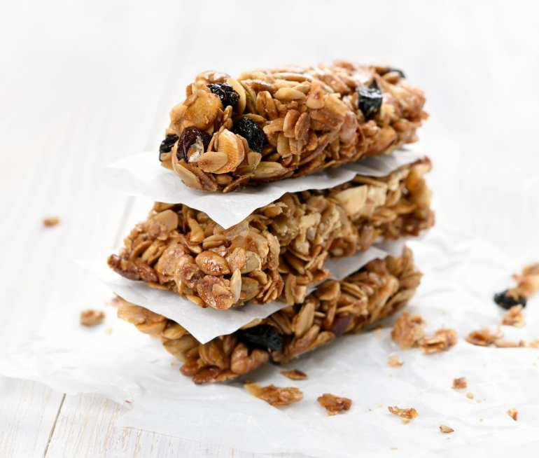 a stack of cannabis infused granola bars on a white wooden surface